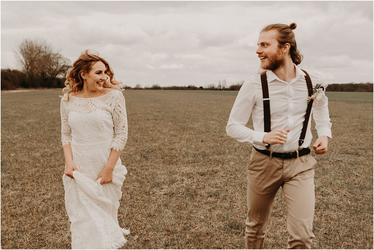 Boho wedding bride and groom run through the fields at The Barns at Lodge Farm
