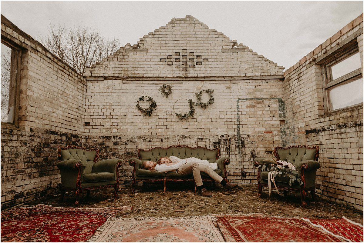 Bride and groom lay together on vintage sofas in abandoned brick building during their Essex boho wedding day