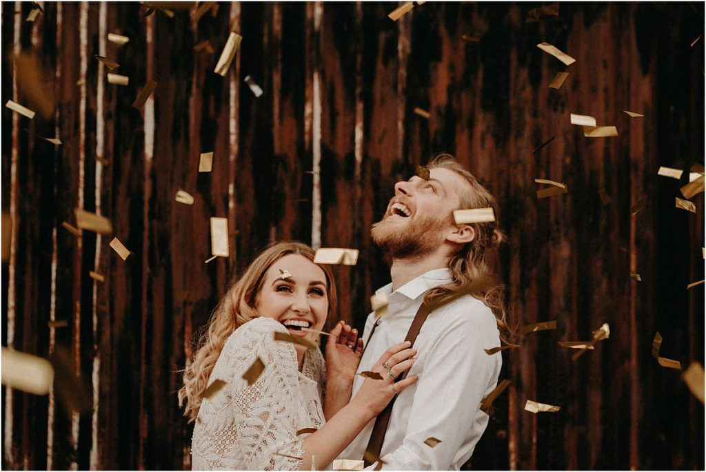 Bride and groom showered in gold confetti on their barn wedding day
