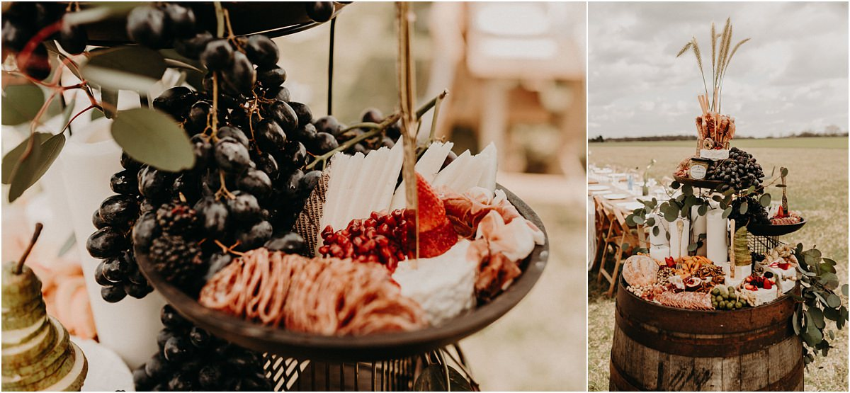 Grazing spread full of artisan foods by Grape & Fig on barrel at field wedding