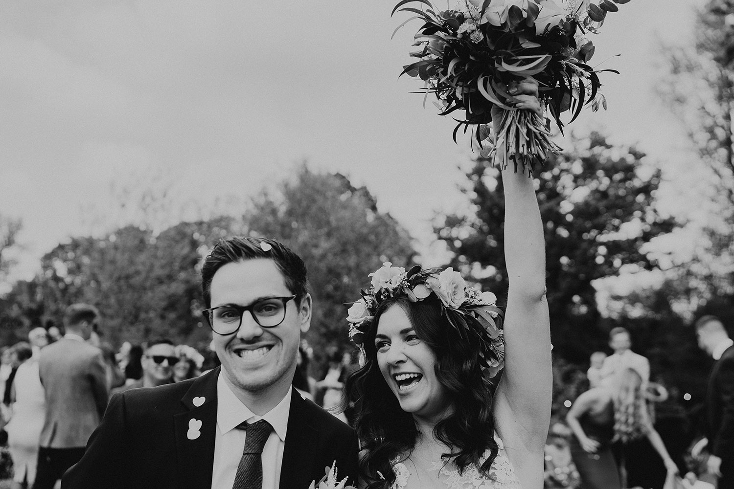 Black and white image of bride and groom as bride punches bouquet into the air in celebration