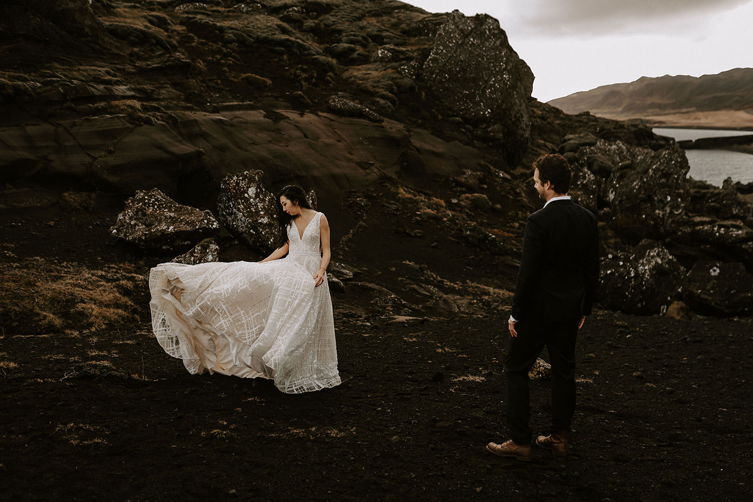 Asian bride's wedding dress blows in the wind in Iceland