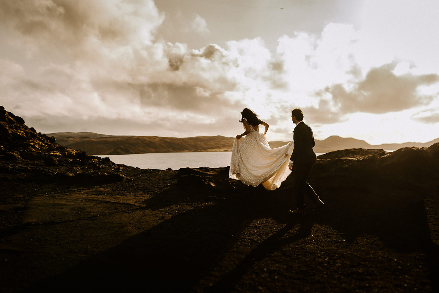Photograph by Iceland elopement photographer of groom holding bride's dress train as they walk together in Iceland mountains