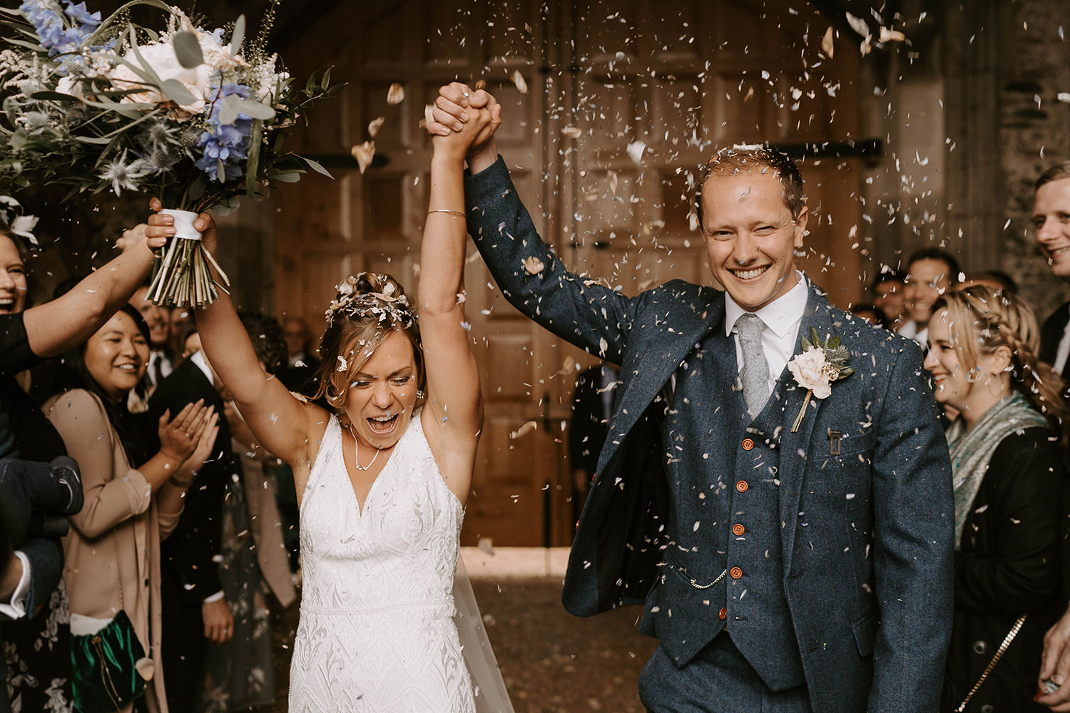 Cheerful bride and groom celebrate holding their hands in the air during confetti throwing
